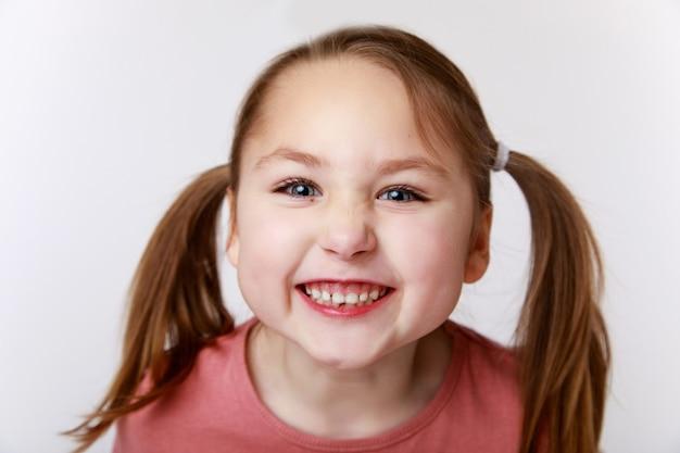 Маленькая забавная эмоциональная девочка с открытой улыбкой и двумя хвостиками