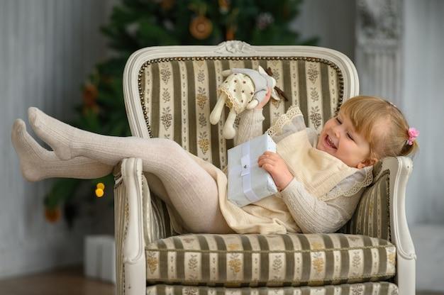 クリスマスツリーの前の椅子で楽しんでいる小さな面白い女の子