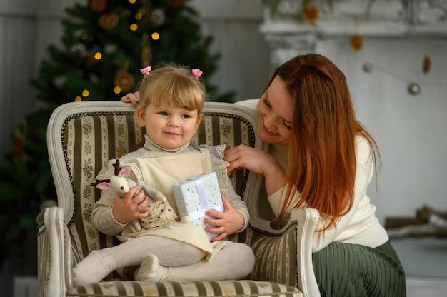 椅子に座っている小さな面白い女の子とクリスマスツリーの前に彼女の素敵な母親