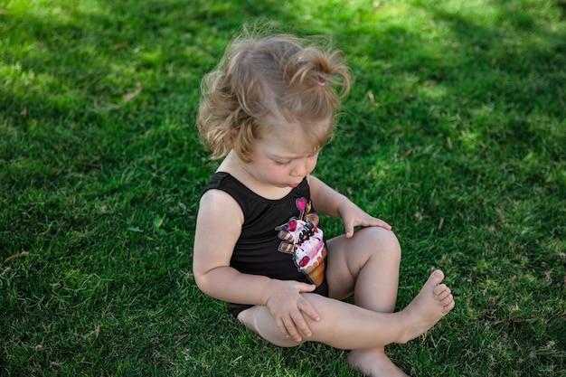 夏の小さな面白い女の子は庭の草の上に座っています