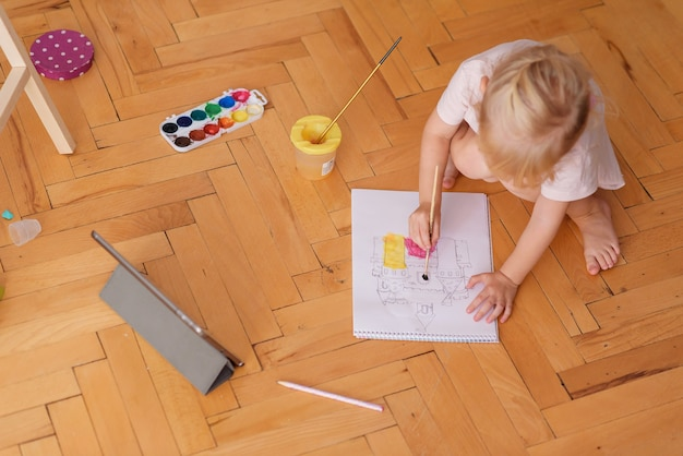Little funny girl painting with paintbrush
