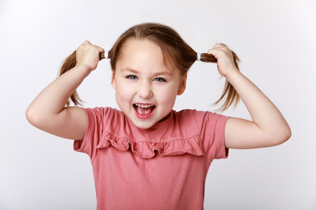 Little funny girl pulling her hair out