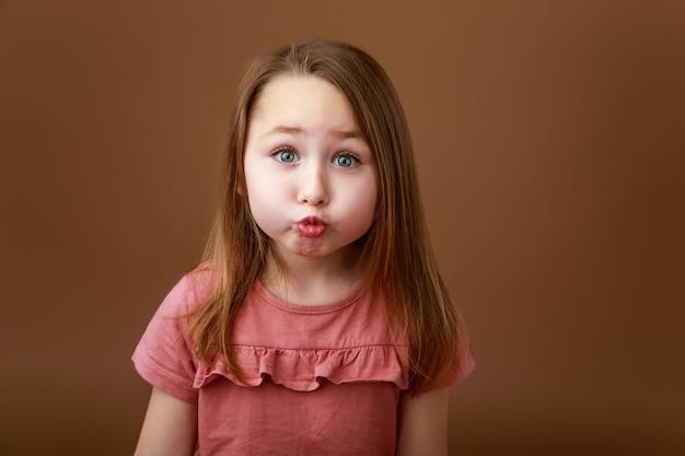 Маленькая забавная девочка, растягивая губы в поцелуе