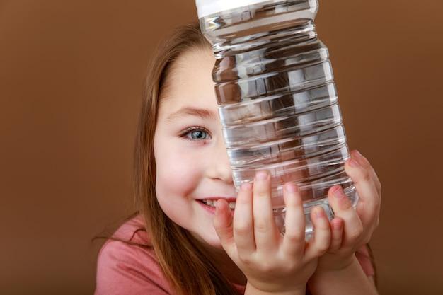 Маленькая забавная девочка с бутылкой воды