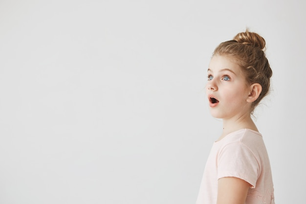 Little funny girl with blonde hair in bun standing with open mouth on street, being shocked seeing fire in neighbor's home.