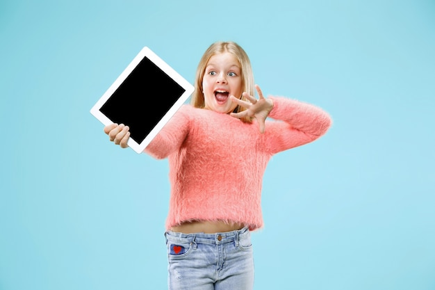 Little funny girl with tablet on blue studio wall