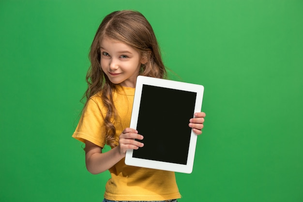 Little funny girl with tablet on green studio background. she showing something and pointing at screen.
