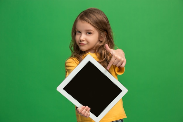 Little funny girl with tablet on green studio wall