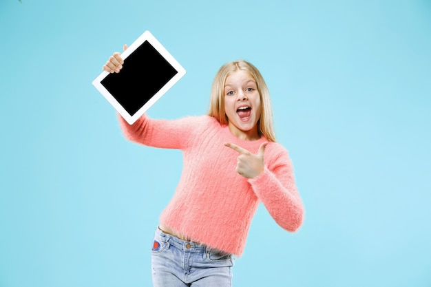 블루 스튜디오 배경에 태블릿 작은 재미있는 소녀. 그녀는 뭔가를 보여주고 화면을 가리켰다.