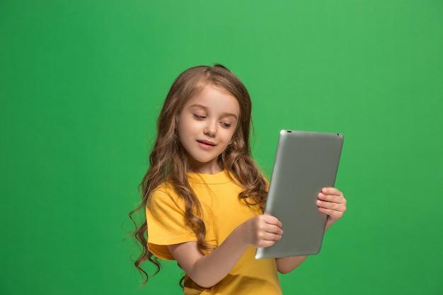 緑のスタジオの背景にタブレットを持つ小さな面白い女の子。彼女は何かを見せて画面を見ています。