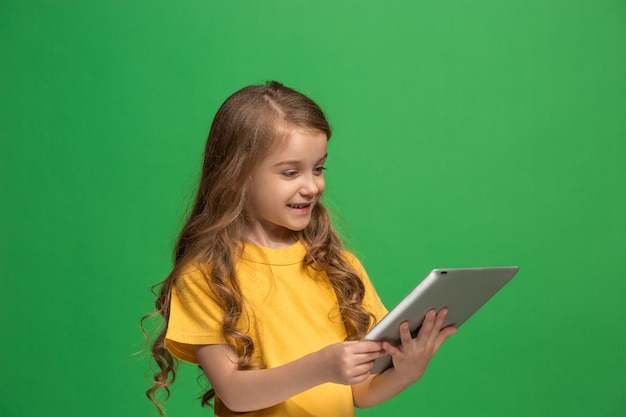 Маленькая смешная девочка с таблеткой на зеленой предпосылке студии. она что-то показывает и смотрит на экран.