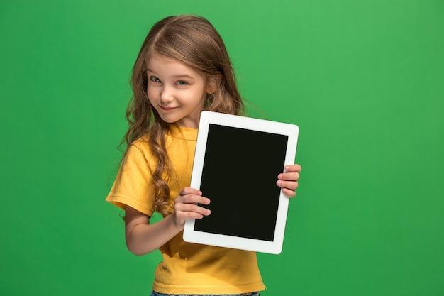 緑のスタジオの背景にタブレットを持つ小さな面白い女の子。彼女は何かを見せて画面を指さしている。