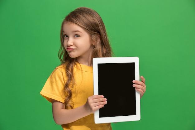 緑のスタジオでタブレットを持つ小さな面白い女の子