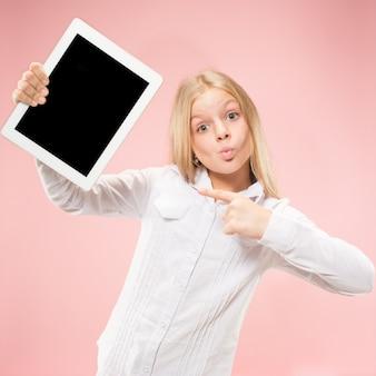 ピンクのスタジオの背景にタブレットを持つ小さな面白い女の子。彼女は何かを見せて画面を指さしている。