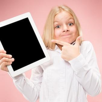 Маленькая забавная девочка с планшетом на розовой студии