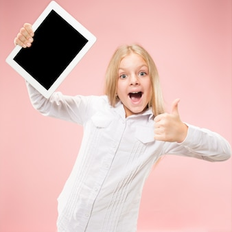 Little funny girl with tablet on pink studio background. she showing something and pointing at screen.