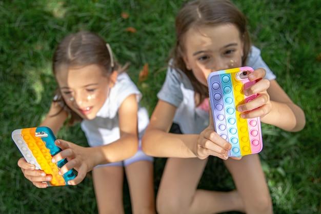 にきびのあるケースに携帯電話を持った芝生の上の小さなおかしな女の子がそれをポップします、流行の抗ストレスおもちゃ。
