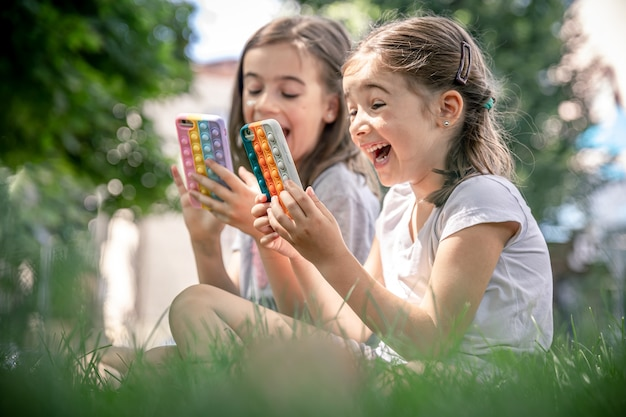 Little funny girls outdoors with phones in a case with pimples pop it, a trendy anti stress toy.