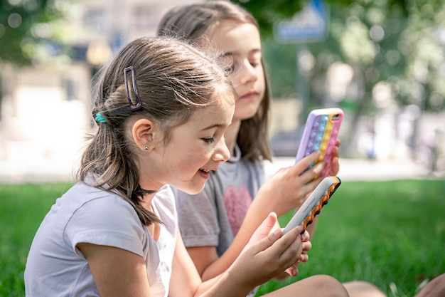 にきびのあるケースに携帯電話を持っている屋外の小さな面白い女の子がそれをポップします、流行の抗ストレスおもちゃ。
