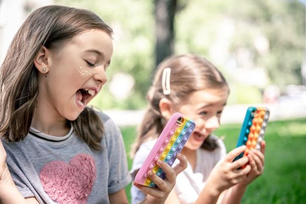 여드름이 있는 케이스에 휴대전화를 들고 야외에서 웃고 있는 어린 소녀들이 유행하는 안티 스트레스 장난감인 팝을 팝니다.