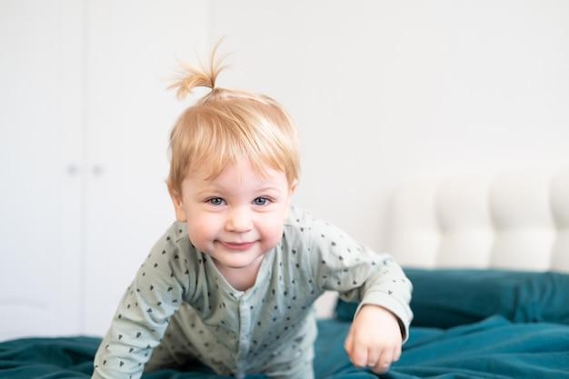 잠 옷 집에서 침대에서 재미 작은 재미 유아 소년, 녹색 침구.