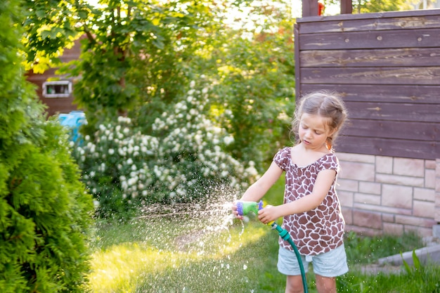 Little gardener girl, she is watering flowers on the lawn near cottage
