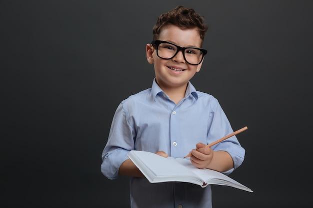 少し天才。眼鏡をかけ、灰色の背景に孤立して立っている間彼の家の割り当てに取り組んでいる活気のあるスマート勤勉な少年