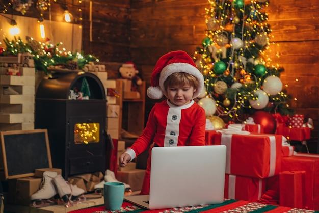 少し天才。サンタリトルヘルパー。小さな男の子のサンタの帽子とコスチュームを楽しんでいます。クリスマスツリーの近くにラップトップを持つ男の子の子供。オンラインでクリスマスプレゼントを購入します。クリスマスの買い物のコンセプト。ギフトサービス。