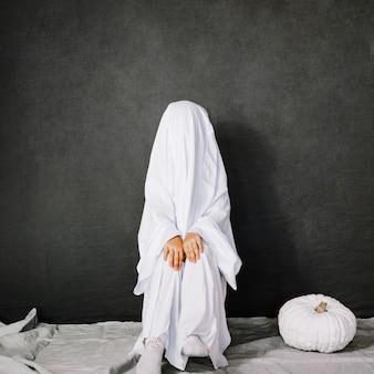 Little ghost near white pumpkin