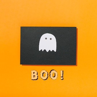 Little ghost on piece of black paper with boo! inscription