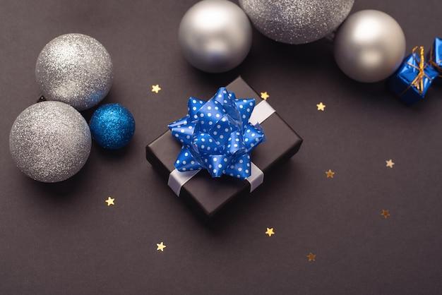 별이 있는 어두운 배경에 작은 선물 상자와 크리스마스 공