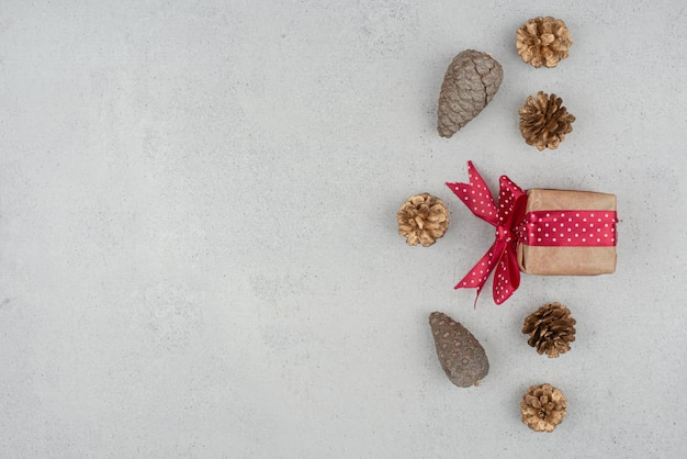A little gift box with red bow and many of pinecones on white background