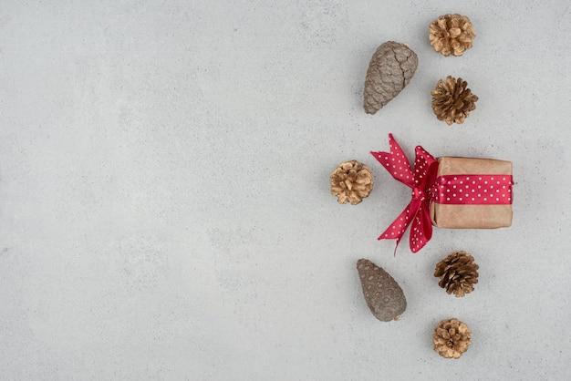 Una piccola confezione regalo con fiocco rosso e molte pigne su sfondo bianco