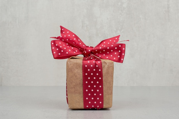 A little gift box with red bow on white background.