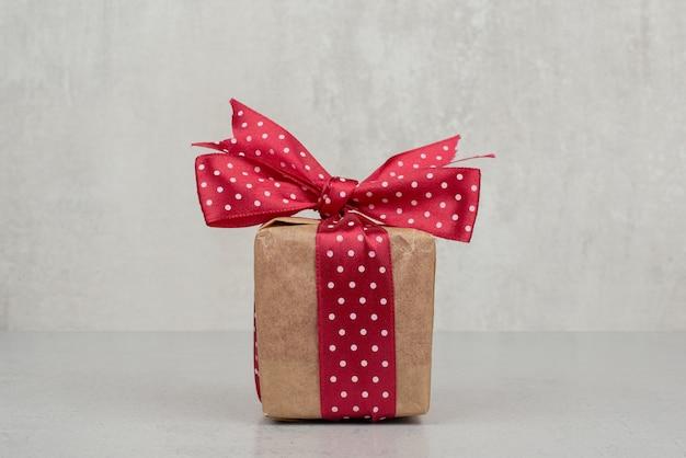 Una piccola confezione regalo con fiocco rosso su sfondo bianco.
