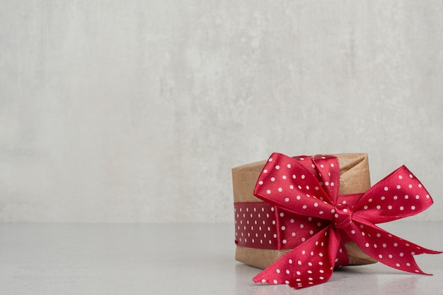 Una piccola confezione regalo con fiocco rosso sul muro bianco.