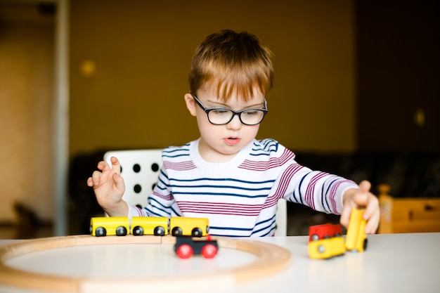 Little ginger child boy in the glasses with syndrome dawn playing with wooden railways
