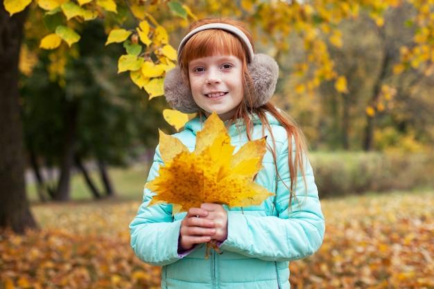 가 공원에 그의 손에 단풍 잎을 들고 생강 소녀