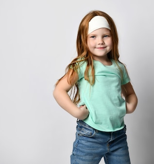 フィットネスヘッドバンドとスポーティーなtシャツを着た小さな生姜女子高生、カメラのポーズをとって両手を握っているジーンズ。スポーツ、アクティブな運動、朝のトレーニング、ウォームアップ愛好家。