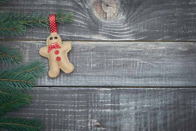 Little gingerbread man hanging on branch of pine tree