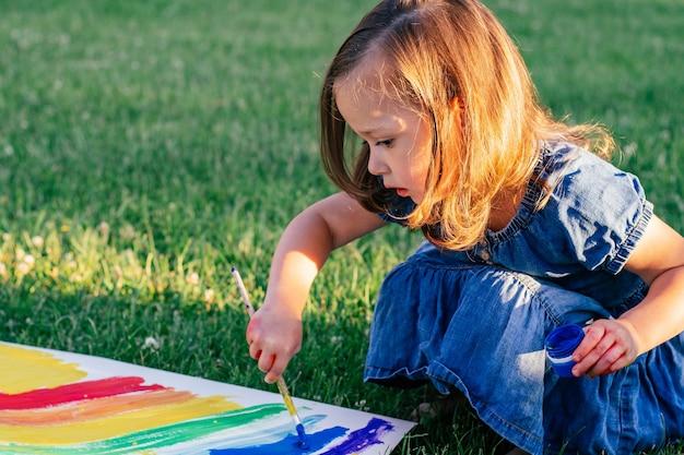 2~4세 어린 소녀는 큰 종이에 무지개와 태양을 칠하고 햇빛 아래 녹색 잔디에 앉아 있다