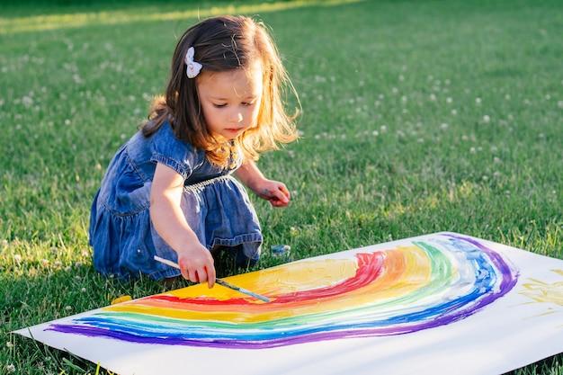 2-4세 어린 소녀는 녹색 잔디에 앉아 큰 종이에 무지개와 태양을 그립니다.