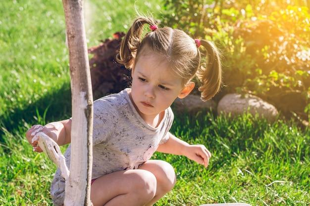 2~4세 어린 소녀는 정원에서 어린 나무 줄기의 밑부분을 브러시로 희게 한다
