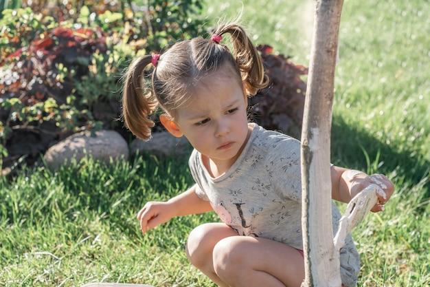 정원에 있는 어린 나무 줄기의 기초를 닦는 브러시로 2-4세 된 어린 소녀