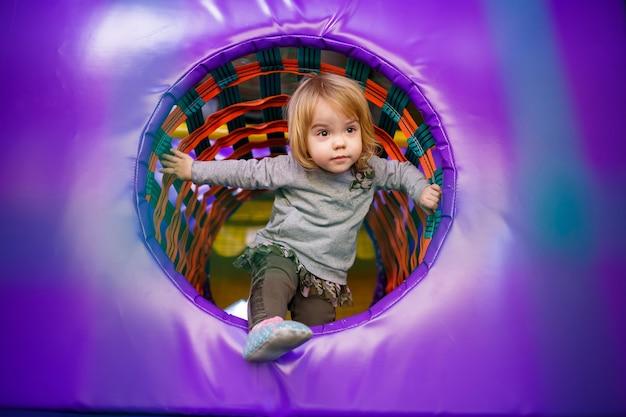 Маленькая девочка 2 лет играет в детской зоне с аттракционами