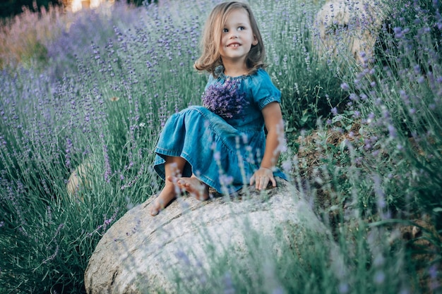 Little girl 3-4 with dark hair in denim dress sits on stone among large bushes of lilac lavender, with bouquet of flowers