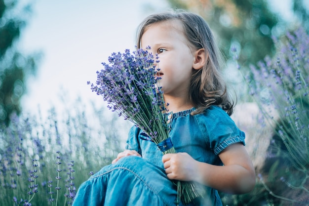 Little girl 3-4 with dark hair in denim dress sits with bouquet of lilac lavender and looks ahead