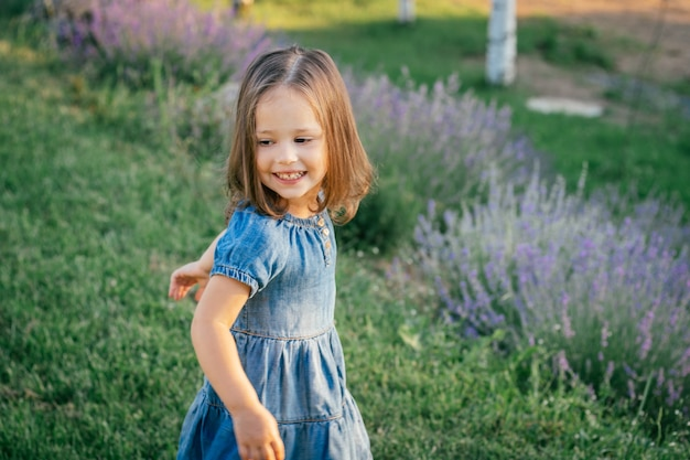 Little girl 3-4 with dark hair in denim dress in sun dancing or running and smiling, among large bushes of lilac lavender