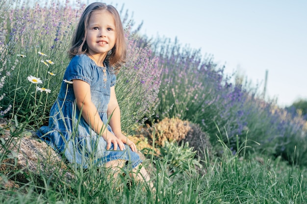 Little girl 3-4 with dark hair in denim dress in sun sits on stone, among large bushes of lilac lavender against sky