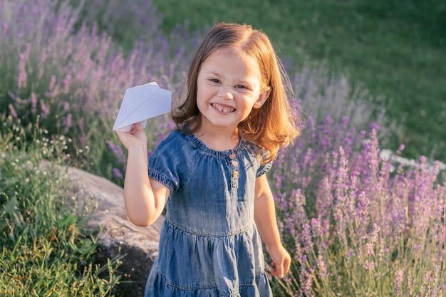 ライラックラベンダーの大きな茂みの中で、太陽の下でデニムのドレスを着た黒髪の少女3-4が紙飛行機を発射します